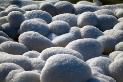 Snowy stones. Covered with hard sunshine Stock Photos