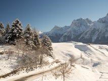 Verschneite Straße in den Bergen Stockbilder