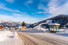 Snowy-Straße, Schnee umfasste Bushaltestelle mit Berg am Hintergrund Skiregion Schladming, Liezen, Steiermark, Österreich, Europa lizenzfreie stockfotos