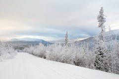 Snowy-Straße zu den weiten Bergen Stockfotos
