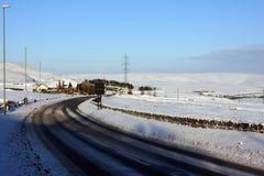 Snowy-Straßenbiegung in einer hügeligen Landschaft Stockbilder