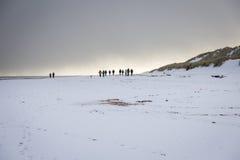 Snowy-Strand mit Gruppe Wanderern Lizenzfreies Stockbild
