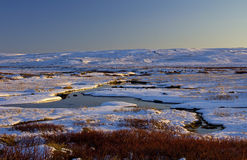 Snowy stream highlighted by evening sunlight, Langahlid, Iceland Royalty Free Stock Photos