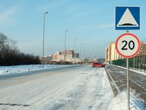 A snowy street with the established traffic signs. 5.20 `Artificial roughness` and 3.24 `Restriction of the maximum speed` 20 km stock photography