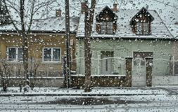 Snowy streets with raindrops. View of some houses covered in snow, while raindrops are on the windshield Royalty Free Stock Photography