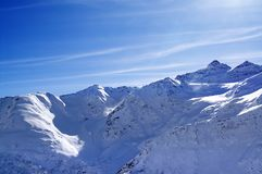 Snowy sunlight mountains at nice evening, view from off piste sl Royalty Free Stock Image