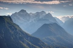 Snowy sunlit Triglav peak and deep valleys Julian Alps Slovenia. Slovenia highest point Triglav peak from north with snowy Rjavina, Cmir and forested Jerebikovec Stock Images