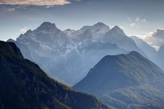 Snowy sunlit Triglav peak and Kot Valley, Julian Alps, Slovenia. Triglav, highest peak of Slovenia, from the north with snowy Rjavina and Cmir peaks, green Royalty Free Stock Photos