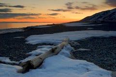 Snowy sunset. Sunset on a winter beach Stock Photo