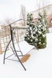 Snowy swing on garden patio, winter scenery Royalty Free Stock Photos