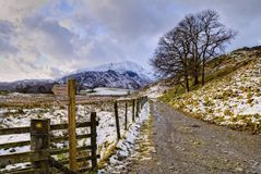 Snowy track and footpath sign. A snowy track and footpath sign in Little Langdale in the English Lake District. Wetherlam can be seen in the distance Stock Images
