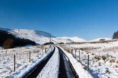 A snowy track leads towards snow capped mountains. A small track leads off towards distant mountains after heavy snowfall stock image