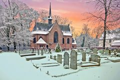 Snowy traditional medieval church in Lage Vuursche Netherlands. Snowy traditional medieval church in Lage Vuursche the Netherlands at sunset Royalty Free Stock Photo