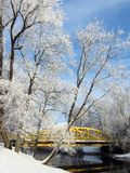 Snowy trees and yellow bridge by river, Lithuania royalty free stock images