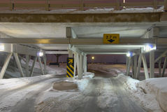 Snowy Underpass. A snow covered underpass leads to a winding road. You can make out lights in the distance on the shore of the river Royalty Free Stock Image
