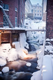Snowy urban waterfall. Closeup of snowy waterfall with slow motion blur between old urban buildings in Winter stock photography