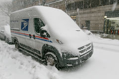 Snowy US Mail vehicle. New York, February 9, 2017: A US Mail van that is parked in the street is getting burried by the falling snow royalty free stock images