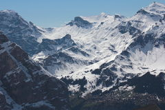 Snowy Valley with a town below. The North face of the Eiger with some greenery at the bottom Royalty Free Stock Images
