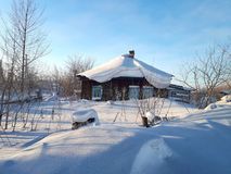 Snowy village house in Siberia. Large snow drifts. Sunny winter royalty free stock photo