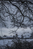 Snowy village through trees Royalty Free Stock Photography