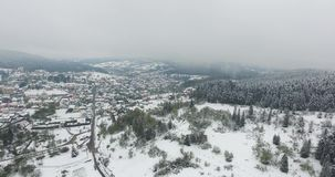 Snowy village in the valley of wooded hills. Aerial view. Snowy village in the valley of wooded hills, winter mountain slopes strewn with snow, tall spruce stand stock video