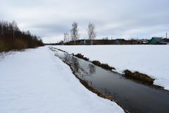 Snowy water channel river stream in the village of birch sky clouds. Spring outside the city, the sound of the water in the pond is melting snow royalty free stock photos