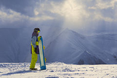 Snowy weather in the mountains snowboarder stands sideways Royalty Free Stock Photography