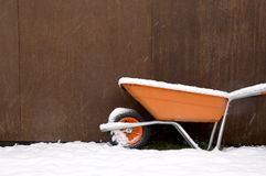 Snowy wheelbarrow. A wheelbarrow leaning against a shed, covered in snow stock photography