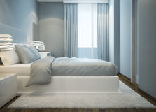 Snowy white bed in blue bedroom Royalty Free Stock Images