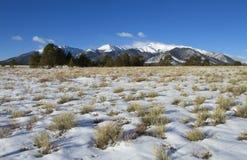 Snowy-Wiese mit Gebirgshintergrund Stockfotos