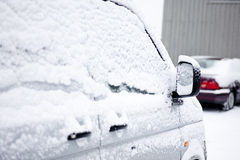Snowy window. Side view of a snowy car with a snow covered rear mirror Royalty Free Stock Image