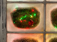 Snowy Windows with red ornament hanging on fir tree with glowing Royalty Free Stock Photos