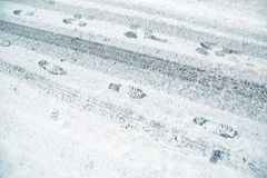 Snowy winter asphalt road with tire trace and shoe prints Royalty Free Stock Photography