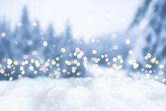 Snowy winter christmas bokeh background with lights and trees