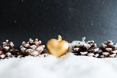Winter christmas decoration with golden heart shaped christmas tree ornament and pine cones. Snowy winter christmas decoration with golden heart shaped christmas Royalty Free Stock Image