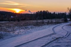 Snow country road in winter. Beautiful winter landscape in the forest. Sunset. Snowy winter Christmas Landscape. Winter sunset with field road and sky Royalty Free Stock Photography
