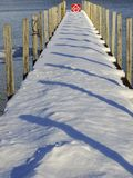 Snowy winter dock with pier shadows Stock Image
