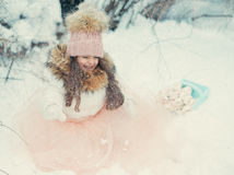 Snowy winter and a girl in a cap. In the forest of snow in winter beautiful girl with long hair in a hat Stock Photos