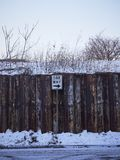 Wooden fence with one way sign in snow stock photos