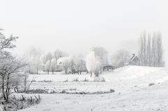 Snowy winter landscape with houses next to a dike. Stock Images