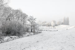 Snowy winter landscape with houses next to a dike. Royalty Free Stock Photos