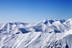 Snowy winter mountains and blue sky, view from ski slope Royalty Free Stock Images