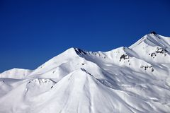 Snowy winter mountains and clear blue sky in sun day Stock Photography