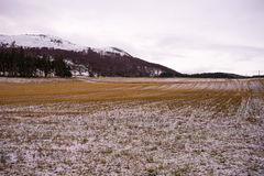 Snowy winter mountains with cloudy skies and farm land in the foreground Royalty Free Stock Photos