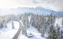 Snowy winter mountains landscape with frosty forest and road. Road to rocky mountain range. Wooden house in pine trees in mountain royalty free stock image