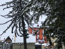 Snowy winter noon. Snow covered trees, the roofs of small houses in the yard. Mountain ski resort Bakuriani.  stock photo