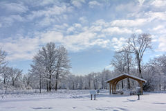 Snowy Winter Park Scene. A snowy winter scene at a park in Toledo Ohio with the snow clinging to the trees and a pretty partly cloudy sky Stock Image