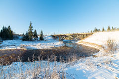 Snowy winter river landscape with metal bridge Stock Photography