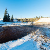 Snowy winter river landscape with metal bridge Royalty Free Stock Images