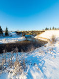 Snowy winter river landscape with metal bridge Royalty Free Stock Photos